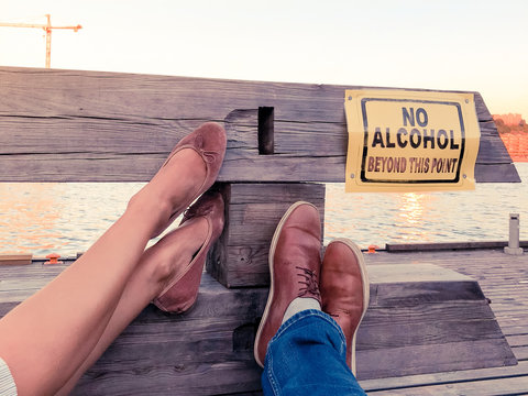 Concept of a young couple decided to stop consuming alcohol. Legs of a man and a women pointing to a sign ''No Alcohol''
