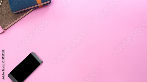 Wall mural smartphone with a notebook on pink background.Top view