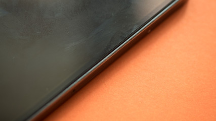 Wall Mural - Smart phone close up on orange background