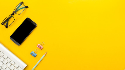 Wall Mural - Mock up smartphone and office accessories on yellow background with copy space.view from above
