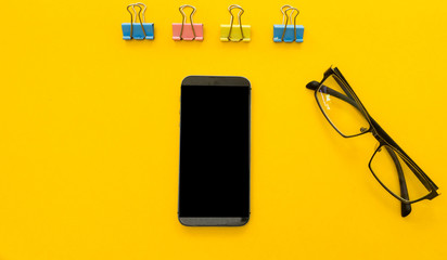 Wall Mural - Mock up smartphone and office accessories on yellow background.view from above