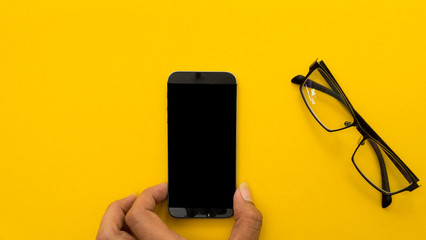 Wall Mural - Mock up smartphone and office accessories on yellow background with hand hold.view from above