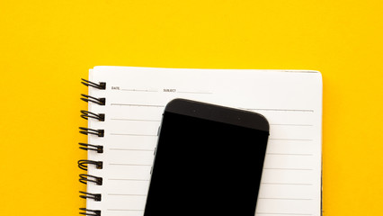 Wall Mural - Smartphone and notebook on yellow background.Close up