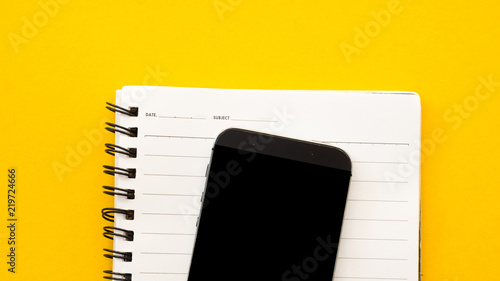 Sticker Smartphone and notebook on yellow background.Close up