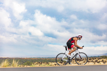 Triathlon cyclist biking on road bike on ironman competition racing against time on nature background landscape. Copy space above athlete on sky.