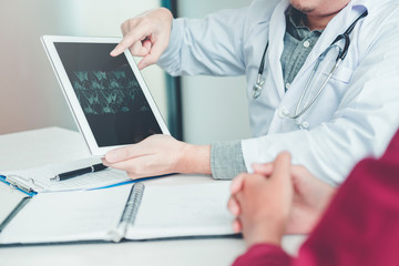 Doctor consulting with patient presenting results x-ray film on digital tablet About the problem of the patient