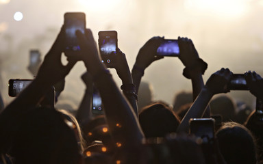 Members of the audience hold up their mobile phones towards the stage at the iHeartRadio MuchMusic Video Awards (MMVA) in Toronto