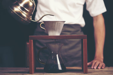 Close up of coffee brewing gadgets on wooden bar counter.