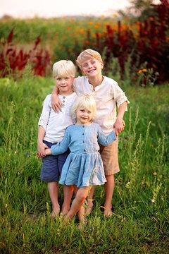 Three Precious Little Blonde Children Holding Hands Outside in the Garden