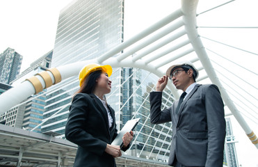 Asian engineer was acting with his secretary on the Business building background.