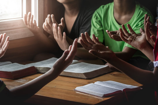 christian children group praying together around wooden table with bible in home room, prayer meeting concept