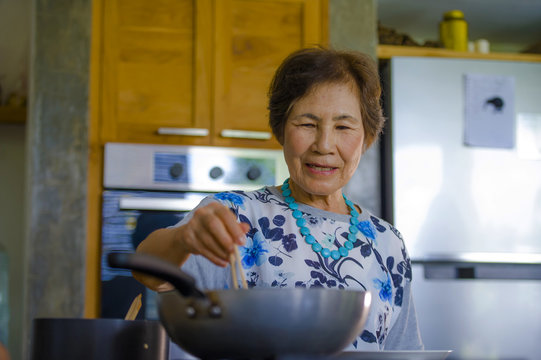 lifestyle portrait of senior happy and sweet Asian Japanese retired, woman cooking at home kitchen alone neat and tidy enjoying preparing meal