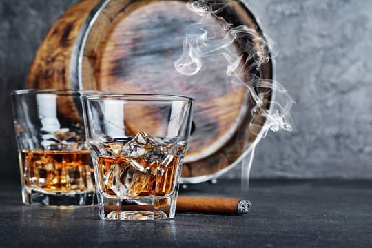 Strong alcoholic drink scotch whisky with ice cubes in old fashion glasses with smoking cigar and vintage wooden barrel in cellar