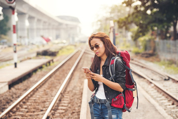 Young woman traveler and backpack stand with using smartphone at the train station