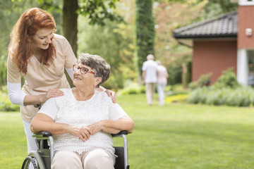 A female volunteer helping a disabled elderly woman in a wheelchair in the garden outside a private luxurious retirement home. Blurred background.