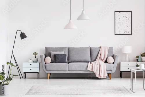 Grey couch with blanket between cabinets in living room interior with  poster and lamps. Real photo 2321ff775