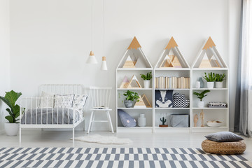 Cute pillows and books on wooden shelves units and a chair by a twin bed in an eco bedroom interior for a teenager