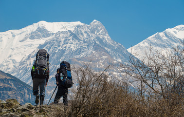 Hikers with backpacks travel in Himalayas mountains range, Nepal.