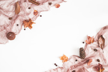 Autumn composition. Brown fabric, autumn flowers and leaves on white background. Flat lay, top view, copy space