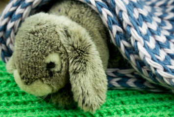 A toy rabbit in a burrow made of knitted fabric.