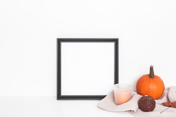 Autumn composition. Photo frame, pumpkins, candles, dried leaves on white background. Autumn, fall, halloween concept. Front view, copy space, square