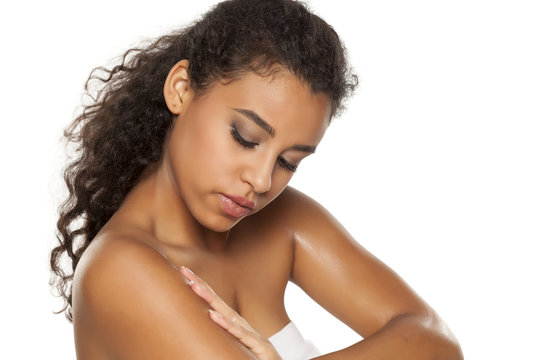 Beauiful dark skinned woman applying body lotion on white background