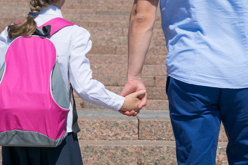 girl with a pink backpack, rises up the stairs, holding her father's hand