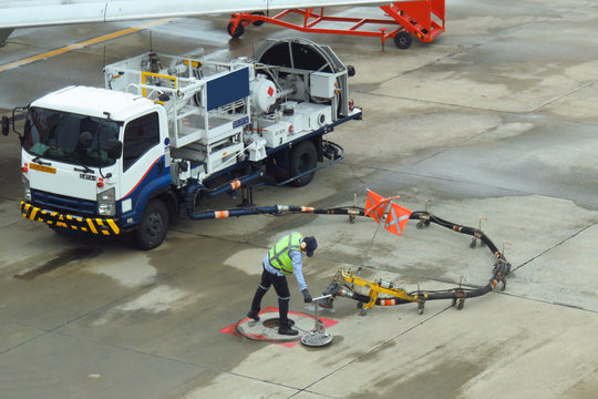 Refuel truck for airplane parked and waiting refuel the airplane on ground in the airport.Ground technician worker refill passenger airplane gasoline fuel from mobile station into an airplane wing