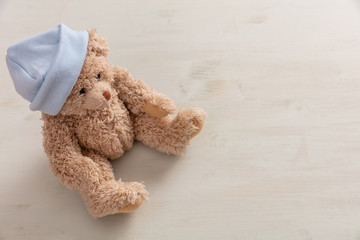 Teddy bear wearing pastel blue cap on wooden background, copy space