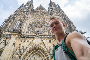 A young, handsome guy with blue crimson makes a selfi in the background of the St. Vitus Cathedral