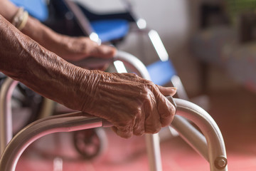 Asian old woman standing with her hands on a walker stand,Hand of patient woman holding a walking aid