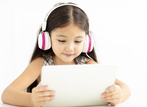 smiling girl in headphone and using  tablet