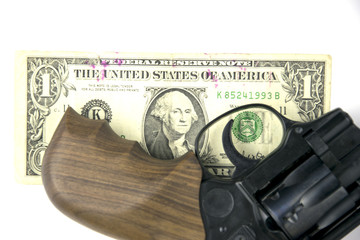 A revolver and a dollar on a white background.