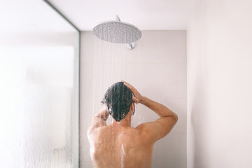Man taking a shower washing hair with shampoo product under water falling from luxury rain shower head. Morning routine luxury hotel lifestyle guy showering. body care hygiene.