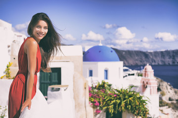 Wall Mural - Europe Greece Santorini luxury travel vacation woman on famous santorini Oia island travel european destination. Red dress elegant lady on jet set holidays. Tourist at balcony over blue dome church.
