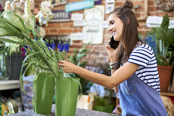 Young florist picking through flowers at the counter while on phone taking order from client