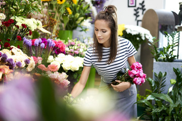 Picture of cute young florist picking flowers for bouquet
