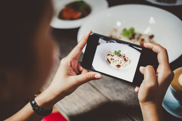 Woman using phone taking photo for food dinner and lunch meal on table