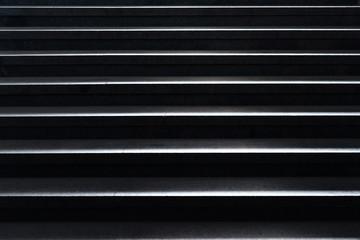 shiny horizontal metal strips on black