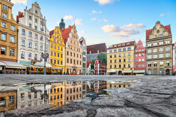 Obraz Old colorful buildings reflecting in a puddle on Rynek square in Wroclaw, Poland - fototapety do salonu