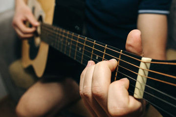 Man at home is playing the guitar. Guys hands are taking the chord on strings. Music making lifestyle concept. Free time hobby for everyone. Retro guitar photo.