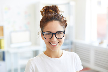 Happy young businesswoman in eyeglasses and white t-shirt gives you toothy smile