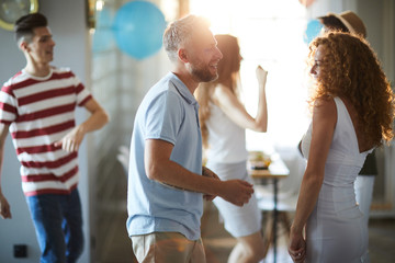 Happy young couple dancing at home party on background of their friends