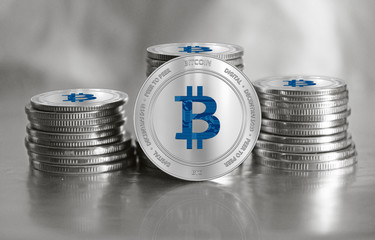 Bitcoin (BTC) digital crypto currency. Stack of silver coins. Cyber money.