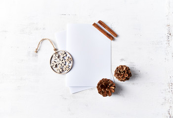 An arrangement of Christmas decorations and blank paper cards on white wooden background. Flatlay. Copy space