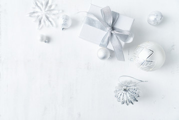 Christmas present with white and silver Christmas decorations. Flatlay. Copy space