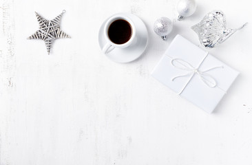 Christmas present, ornaments and a cup of coffee on white painted wooden background. Symbolic image. Flatlay. Copy space