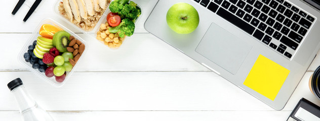 Tuinposter Eten Healthy food in meal box set on working table with laptop