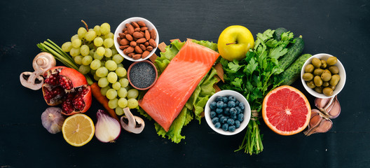 A set of healthy food. Fish, nuts, protein, berries, vegetables and fruits. On a black wooden background. Top view. Free space for text.