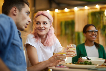 Young couple having drinks by served table at dinner in cafe and discussing something
